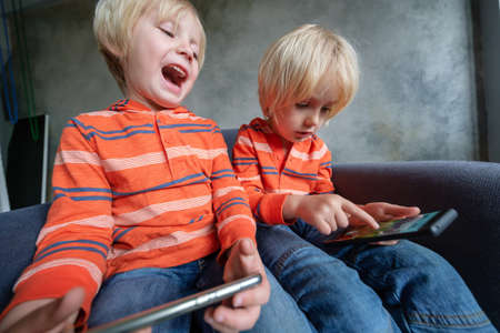 Two brothers are watching or playing or learning something in a smartphone