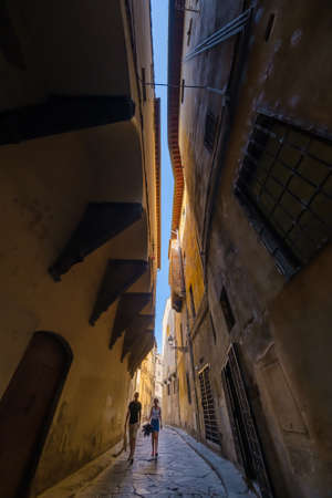 Tourists couple explore narrow street of historic center of Florence, Italy. Bottom view