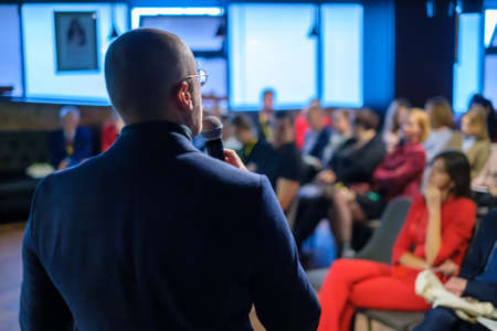 Male presenter speaks to audiences at seminar Stock Photo