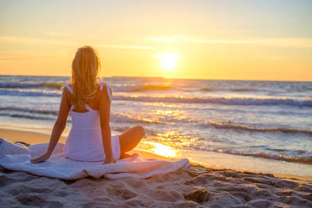 Back view of relaxed female traveler in summer dress sitting on blanket on sandy shore and admiring picturesque sunset over waving sea Foto de archivo