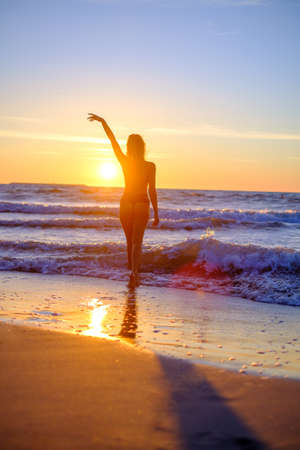 Back view of anonymous female tourist in swimwear standing on seashore and enjoying sunset with raised arm during summer vacation Foto de archivo
