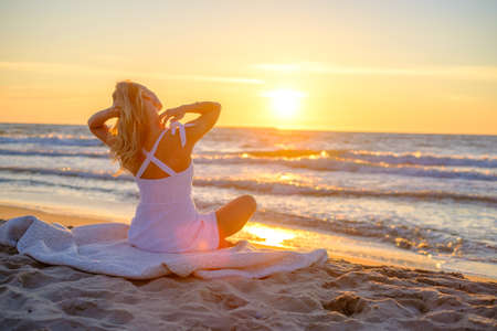 Back view of relaxed female traveler in summer dress sitting on blanket on sandy shore and admiring picturesque sunset over waving sea
