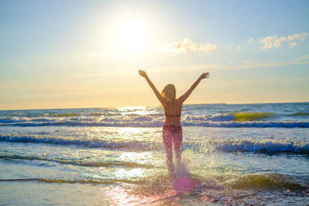 Back view of anonymous female in bikini running to sea water and enjoying sunny weather with raised arms Foto de archivo