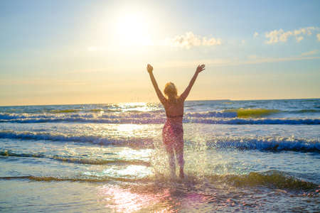 Back view of anonymous female in bikini running to sea water and enjoying sunny weather with raised arms