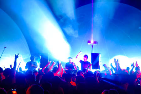 Male DJs engaging dancing crowd under colorful lights during music festival in nightclub