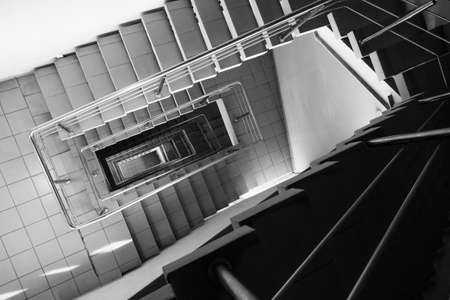 Black and white tiled stairway with metal railing leading down inside contemporary building Stock fotó