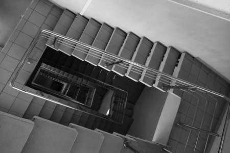 Black and white tiled stairway with metal railing leading down inside contemporary building