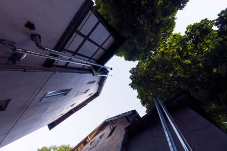 From below residential buildings with pipes and green trees located against cloudless sky on street of town in summer 免版税图像