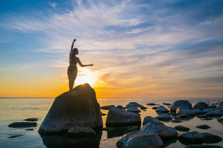Back view of slim female dancing with raised arms on rock near sea against cloudy sunset sky