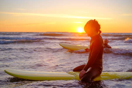 Side view of man in wetsuit sitting on surfboard and resting in sea while surfing with friend during sunset Stockfoto