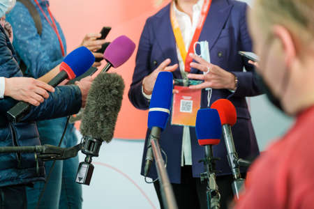 Unrecognizable female entrepreneur surrounded with reporters with microphones delivering speech during interview at business seminar
