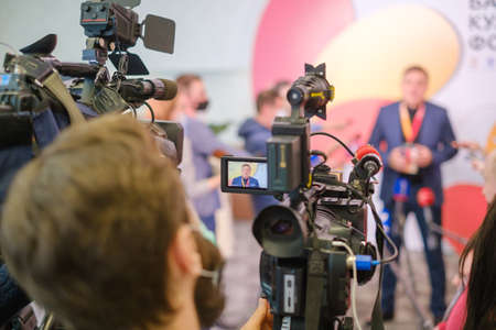 Professional cameras shoot male entrepreneur speaking with reporters during business seminar in modern hall