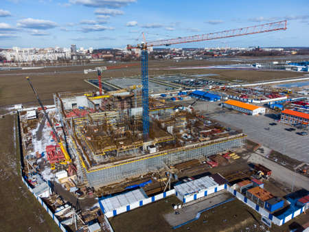 Drone view of tall crane located in middle of construction site near unfinished building in city outskirts