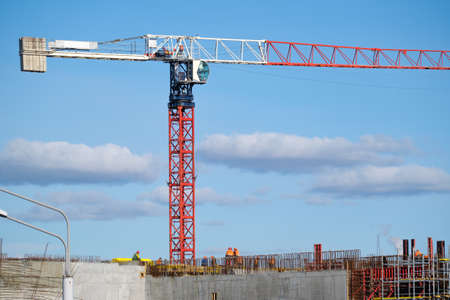 Tall crane located near unfinished building walls with builders against cloudy blue sky on construction site