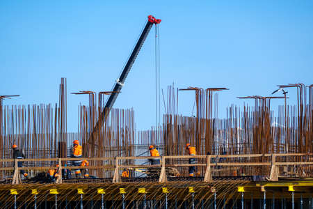 Group of contractors in uniform walking on bridge outside unfinished building against cloudless blue sky on construction site Stockfoto