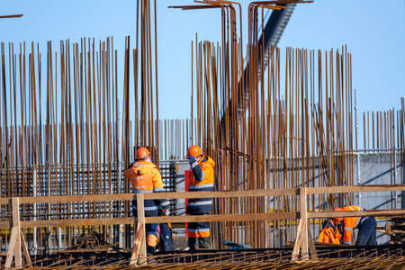 Anonymous male builders in uniform working on bridge near metal poles against cloudless blue sky on construction site Stockfoto