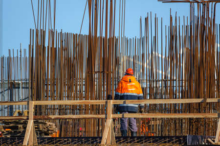 Anonymous man in uniform working on bridge near metal poles outside unfinished building on sunny day on construction site Stockfoto