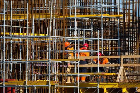Back view of anonymous men in uniform walking near wooden railing and metal poles during work on construction site Stockfoto