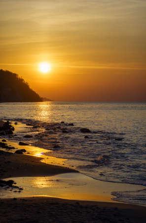 Beach and sea under sunset sky
