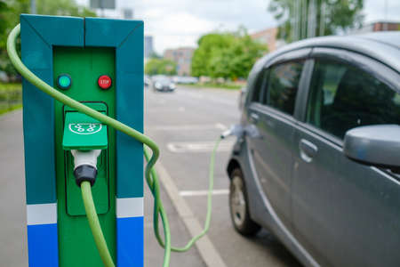 Charging station and electric vehicle on parking lot Stockfoto