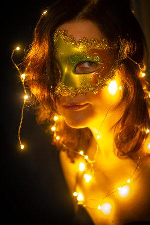 Charming woman in Venetian mask looking at camera