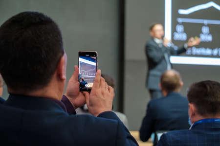 Unrecognizable man shooting speaker during business seminar
