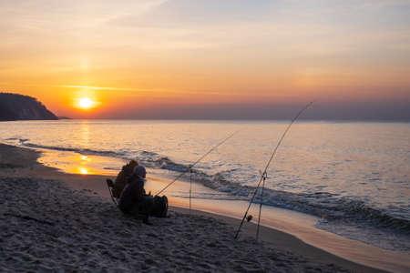 Unrecognizable fishermen catching fish in sea Stockfoto