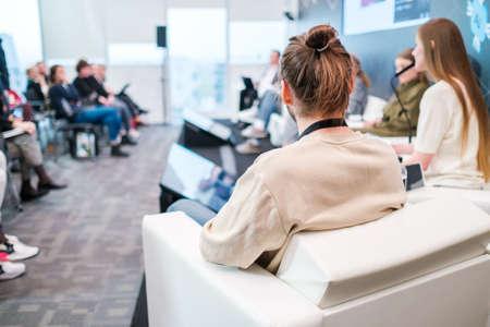 Unrecognizable man listening to speaker during business seminar