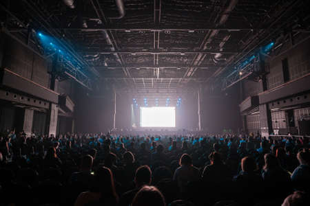 Audience sitting in front of stage with screen