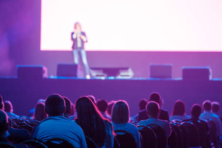 Audience listening to speaker in neon light Stockfoto