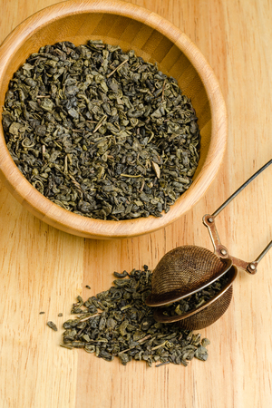 tea filter: Green tea, dried leaves with filter, on wooden