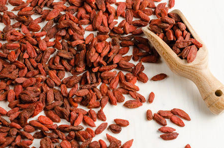 goji berry: Goji berry dried on table, with spoon, closeup background