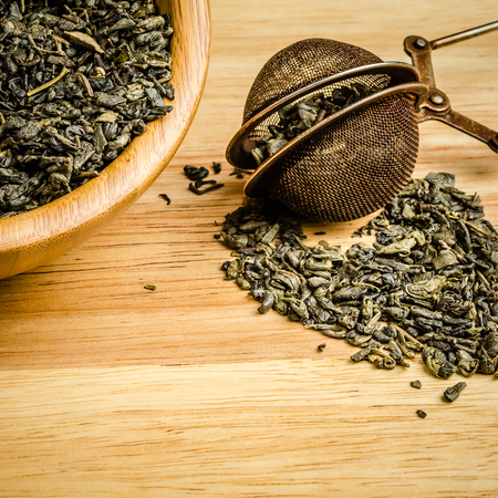 green tea, dried leaves with filter, on wooden background