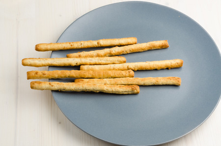 gressins: rustic breadsticks in a dish on wood table, close up, background