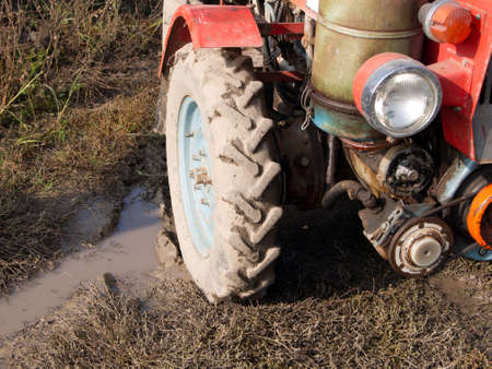 outside machines: Small tractor with the manager stopped by the lake. Stock Photo