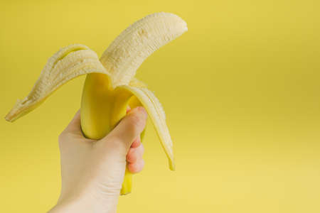 peeled banana: peeled banana in hand on yellow background