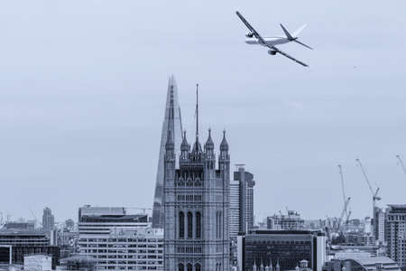 Airplane over new and old tower in London.