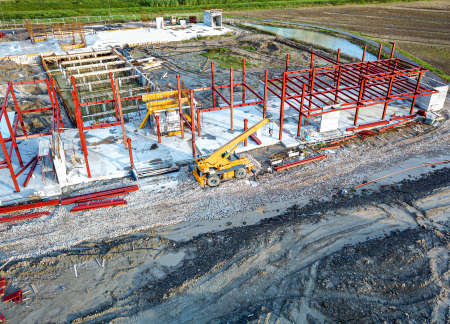 Aerial view of a construction site with heavy machinery for material lifting. Stock Photo