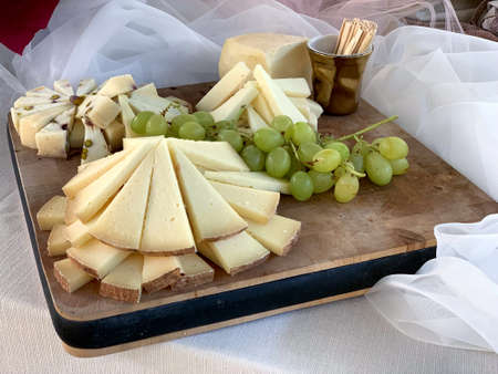 Food concept: cheeses and grapes on wood chopping board.