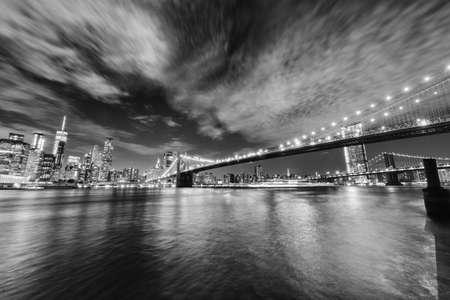 Manhattan skyline and Brooklyn Bridge by night . Фото со стока