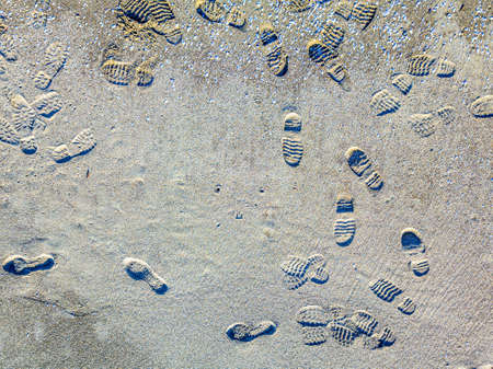 Footsteps of feet on the beach.