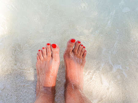 Feet with colored nails of red enamel in the crystal clear sea of the Maldives.