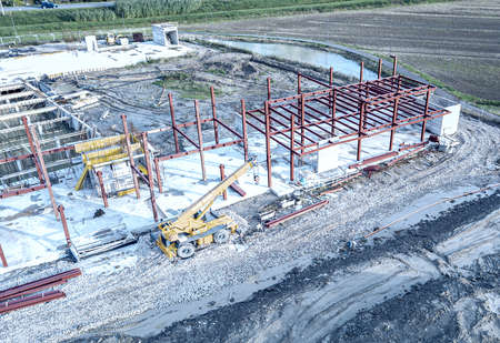 Aerial view of a construction site with heavy machinery for material lifting. 스톡 콘텐츠