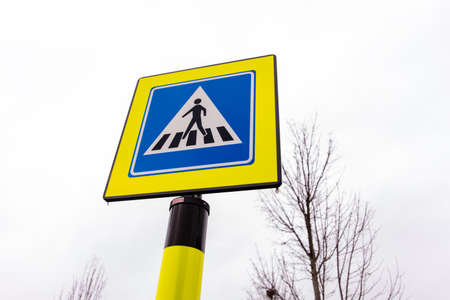 Pedestrian crossing traffic sign in neon yellow and blue colors in the Netherlands