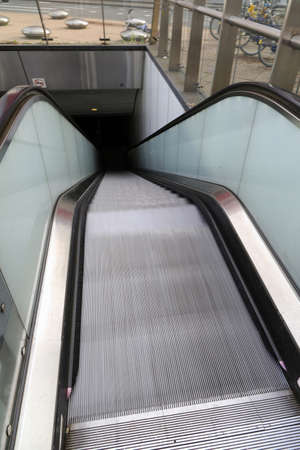 Moving escalator at the metro in Rotterdam with lots of steel and glass details Banco de Imagens