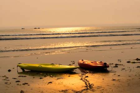 Two kayaks sit on the beach at the Hobuck Beach Resort, near Neah Bay.  The late afternoon sun shines on the scene.