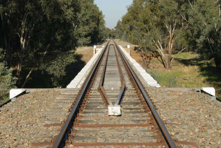 sleepers: a railway bridge crossing over a dry creek in the country with trees