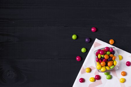 Colorful candies on dark wooden background