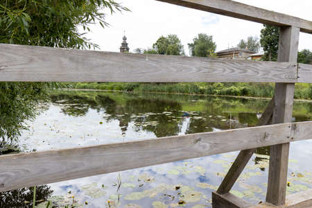 Pond with still water and wooden bridge
