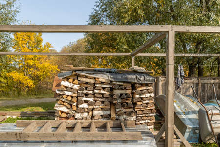 Firewood in woodpile, prepared for Winter. Pile of firewood. The firewood background. A stack of neatly stacked, dry firewood outdoors.